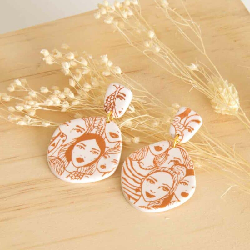 witte oorbellen van klei met gezicht in bronzen print