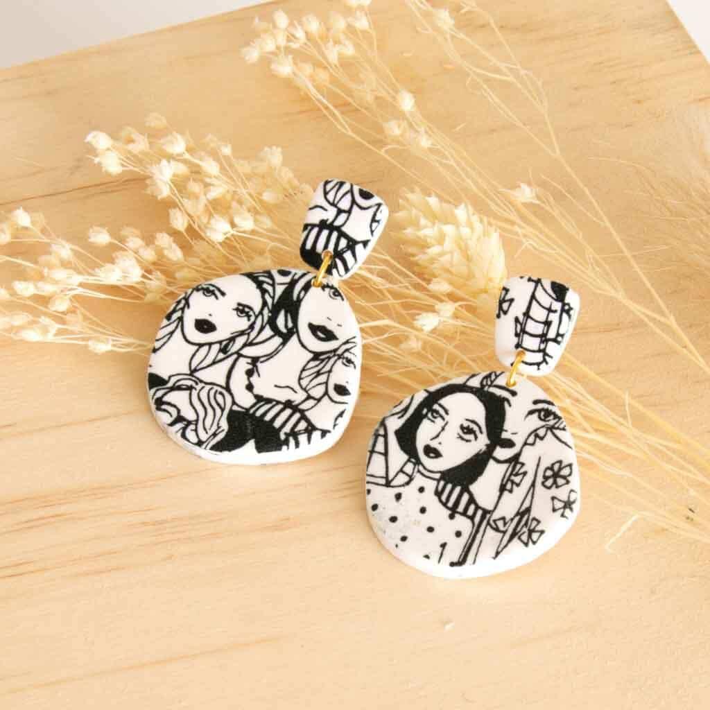 witte oorbellen van klei met gezicht in zwarte print
